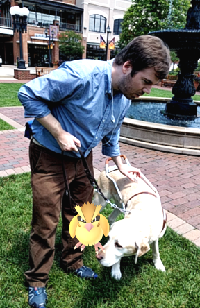 Aaron Preece stands with his guide dog Joel and a Pidgie Pokemon