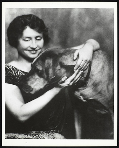 Helen Keller with her arms around a big dog, circa 1925