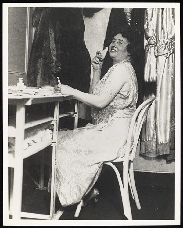 Helen Keller in her vaudeville dressing room. She is seen sitting with her head tilted slightly back as she faces slightly towards the camera. She is applying powder with her right hand, while in her left she holds a cosmetic item. Her left hand is leaning on a table in front of her that is covered with other make-up items. She wears an ankle length, sleeveless shimmering dress that is loose except at the waist. A fur coat and silk or satin items of clothing are visible behind her.
