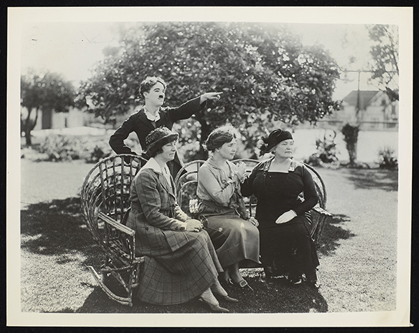 Viewed outdoors, Charlie Chaplin stands behind Polly Thomson, Helen Keller and Anne Sullivan Macy who are all seated on wicker chairs. Their faces are seen in profile as they look towards the right of the image, in the direction that Chaplin is pointing. The women's skirts and dresses are long. Thomson and Macy wear hats. Macy is manually signing into Keller's right hand.