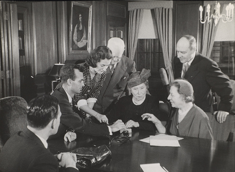 Left to right are: unidentified man, M. Robert Barnett (AFB Executive Director), Marta Sobieski, Peter J. Salmon (Executive Director, Industrial Home for the Blind, Brooklyn), Helen Keller, Polly Thomson, and Gregor Ziemer. The room has wood panelling and a painting of Helen Keller by Albert H. Munsell is visible in the background. Image from documentary Helen Keller in Her Story.