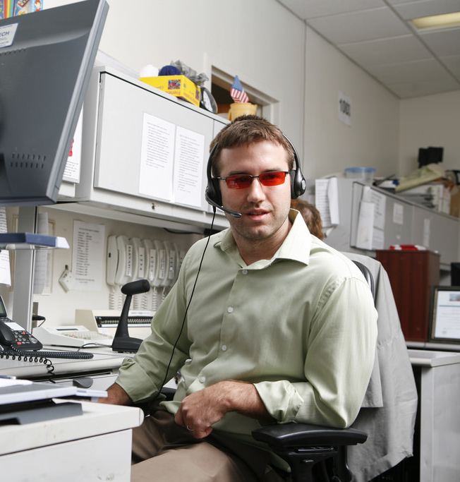 A man wearing tinted glasses and a headset sits in an office.