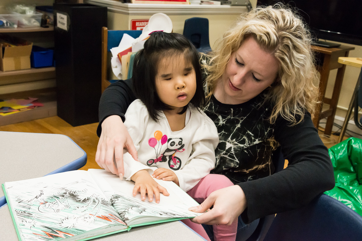 A teacher helps a young girl read a braille book.