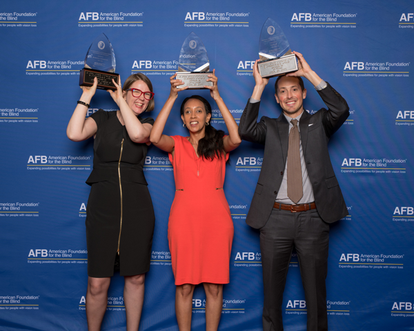 Holding their Helen Keller Achievement Awards above their heads, from left to right, Jenny Lay-Flurrie, Haben Girma, and Jeffrey Wieland.