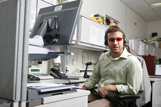 Young man sitting at cubicle desk wearing headset.