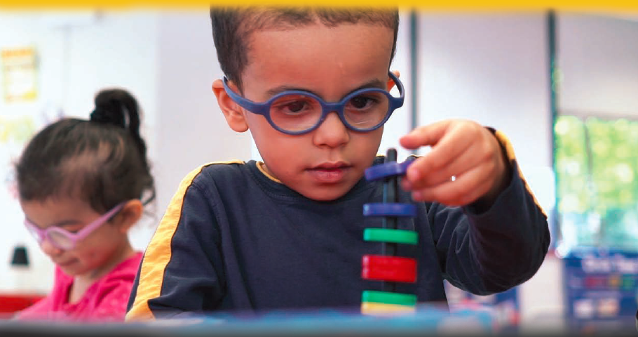 Young boy in classroom playing with stackable rings.