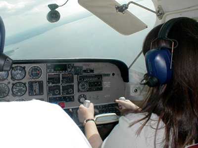 Figure 1: A rear view of Courtney Smith wearing headphones and grasping the steering wheel of an airplane as she sits in front of an instrument panel full of dials.