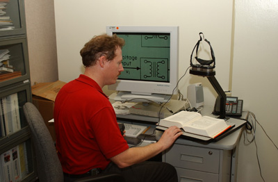 Figure 4: Paul Mogan sitting at a desk with the Jordy mounted on a stand over a large book, while a magnified electrical diagram is displayed on the computer screen.
