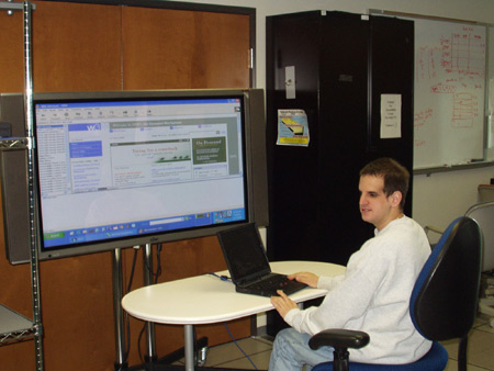 Randy Horwitz working on a laptop computer, with part of an IBM web page projected on a large screen.