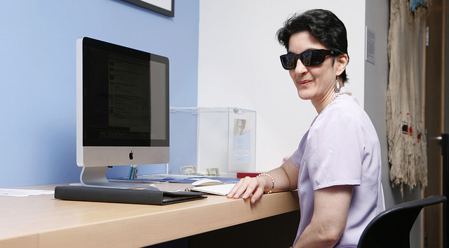 woman seated at her computer work station, wearing sunglasses