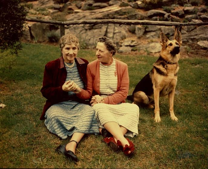 Helen Keller and Polly Thomson, seated outside on the grass with German Shepherd dog nearby, circa 1955