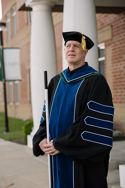 Kirk Adams, standing with his cane, wearing academic cap and gown.