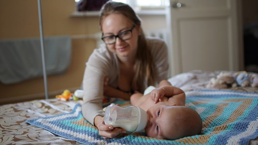 Young mom with glasses feeds her baby with milk in a bottle. Feeding baby.