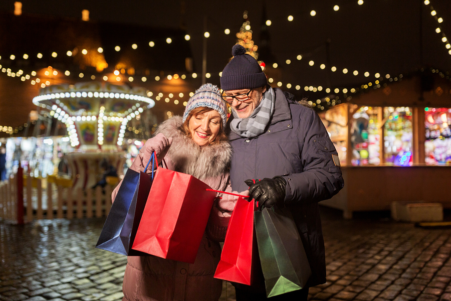 Elderly couple at outdoor market. Behind them are lighted stalls. They are holding shopping bags, looking inside of them and smiling.