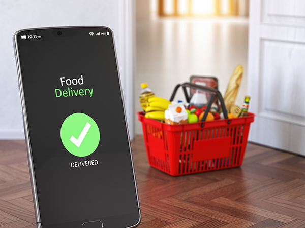Smartphone in the foreground with a generic food delivery app on the screen. In the background is a shopping basket of food.