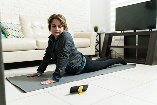 Senior woman watching online workout tutorials on smartphone and exercising at home.