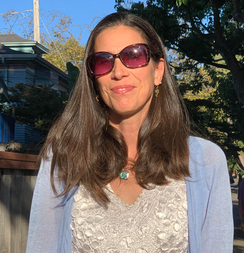 Rachel Longan. Woman with long brown hair. She is standing outside, wearing sunglasses, a light blue cardigan, and white blouse.
