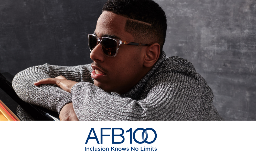 AFB 100. Inclusion knows no limits. Matthew Whitaker, a young black man wearing dark glasses and a grey turtleneck sweater sits in front of and is leaning onto a piano.