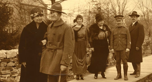 photograph from 1919, just after World War I. Helen Keller has the arm of a newly blinded soldier. He has a bandage over his left eye and is using a cane to help him walk. They are walking down a woodsy path in Baltimore, Maryland. Behind them is a stone wall and a large house with many windows, which is the Red Cross Institute for the Blind. Bringing up the rear, also on the path, are Annie Sullivan, Polly Thomson, and two other men, one in a military uniform.