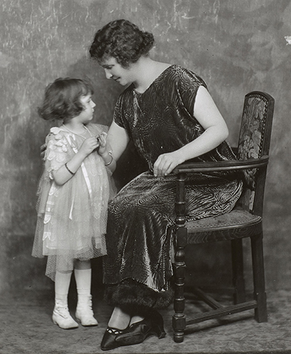 Helen Keller seated in three quarter profile, possibly in a photographer's studio. She is seated in a chair that is sideways to the camera. She is wearing a loose, shimmering dress that is dark and has a boat neck. Keller is leaning over and has her arm around the back of a young girl who is wearing a light colored organza-type fabric dress with ribbons. Keller's dark shoes and the child's light-color boots are typical of the early 19th century.