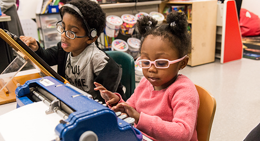 Two students sitting at a classroom table. The boy is wearing headphones and working on a tablet, and the girl is using a braillewriter.
